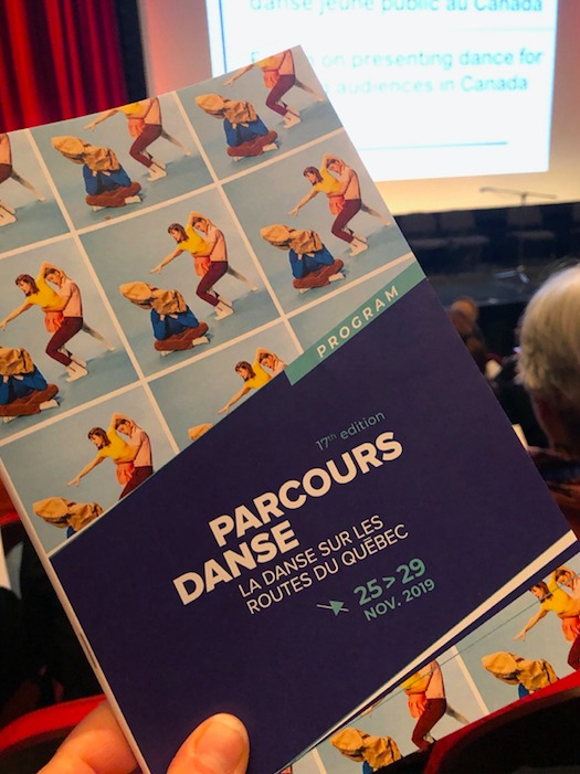 Parcours Danse program held up in front of stage